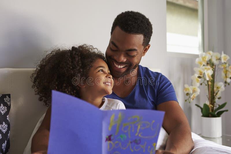Счастливые папа и дочь в кровати с карточкой на утре дня рождения стоковые фото