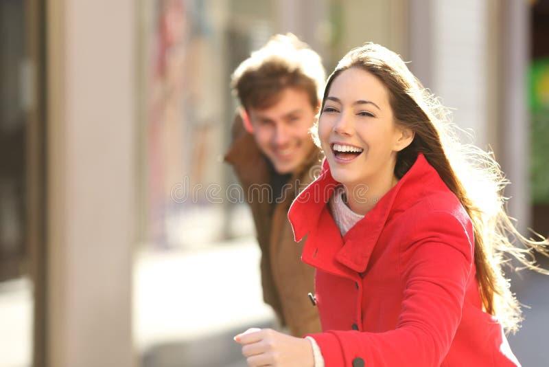 Счастливые пары бежать в улице стоковое изображение rf