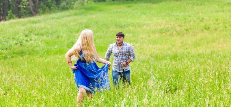 Счастливые пары бежать на луге в природе лета стоковые изображения rf