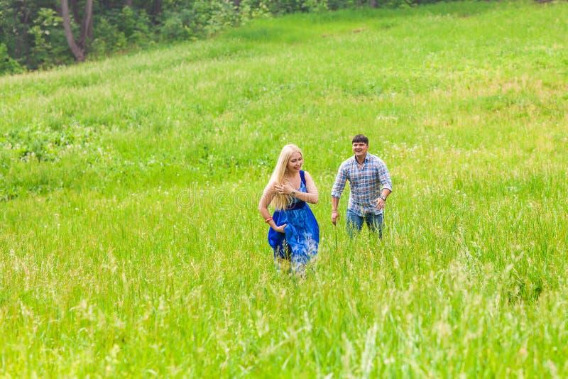 Счастливые пары бежать на луге в природе лета стоковое фото rf