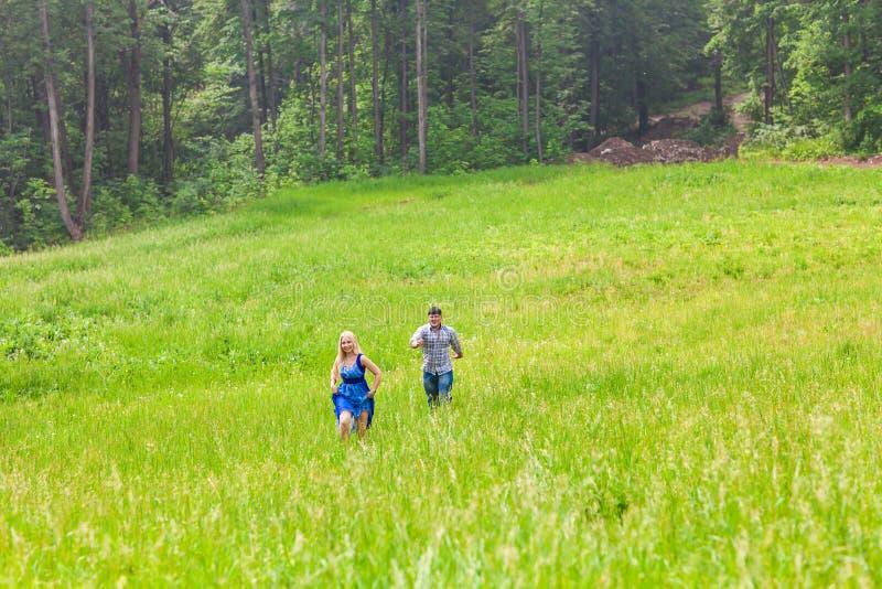 Счастливые пары бежать на луге в природе лета стоковые фотографии rf