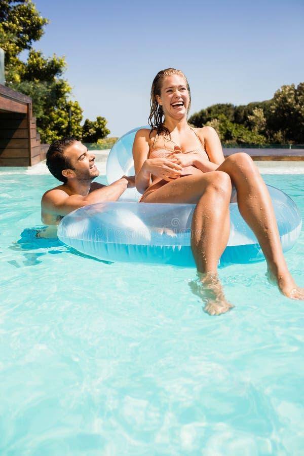 Счастливые пары в бассейне с lilo стоковые фото