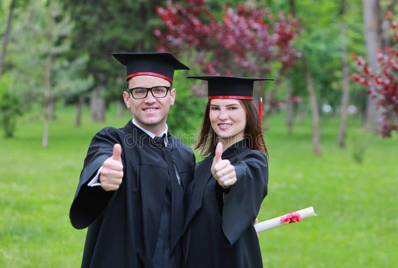 Счастливые пары в выпускном дне стоковые фотографии rf