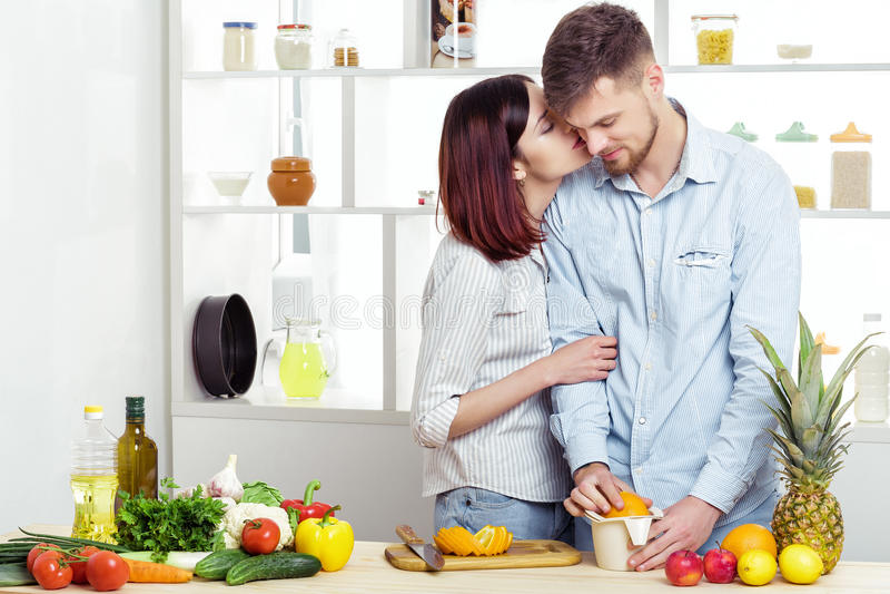 Счастливые пары в влюбленности в кухне делая здоровый сок от свежего апельсина целовать пар стоковые фотографии rf
