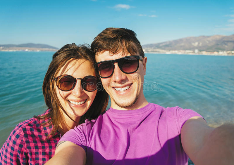 Счастливые пары в влюбленности принимая автопортрет на пляже стоковая фотография