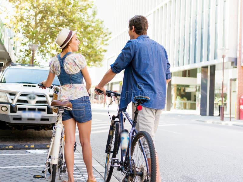 Счастливые пары в городе с велосипедом стоковые фотографии rf
