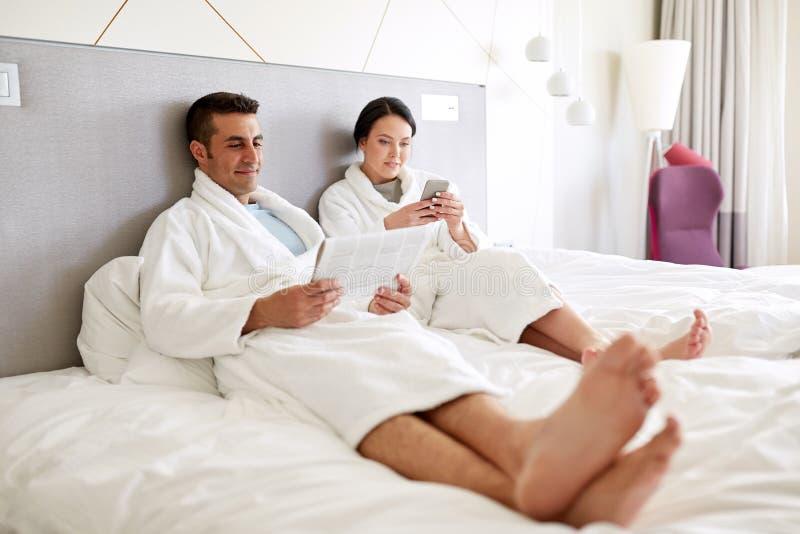 Счастливые пары в кровати дома или гостиничном номере стоковое фото rf