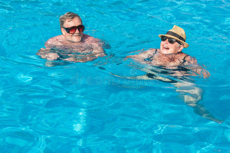 Счастливые пары в плавательном бассеине стоковое изображение