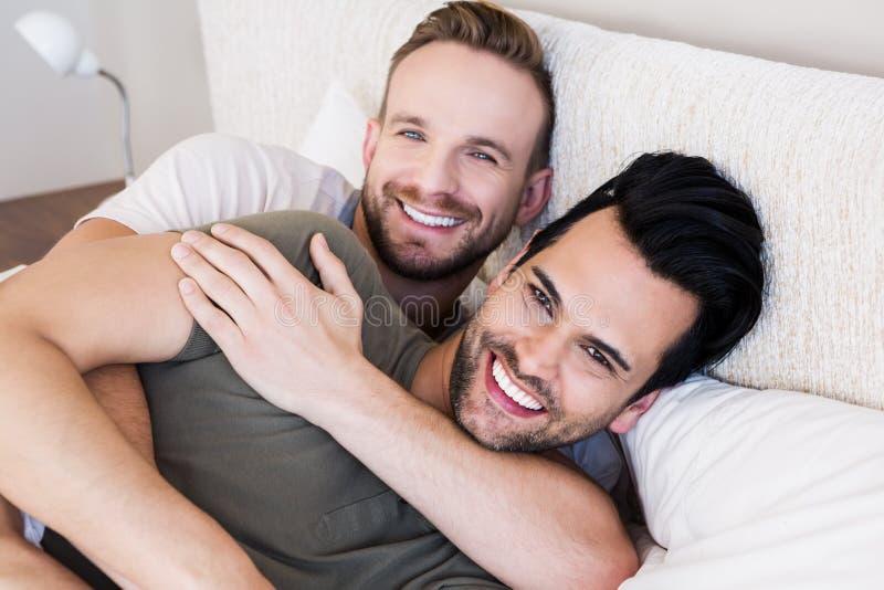 Счастливые пары гомосексуалиста лежа на кровати стоковое фото rf