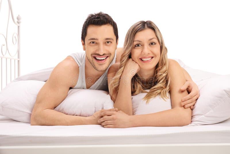 Счастливые пары лежа в кровати и смотря камеру стоковые фотографии rf