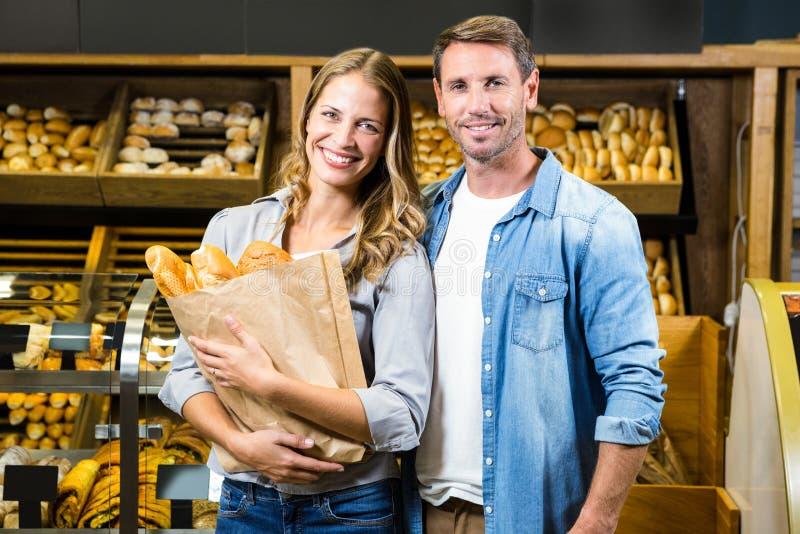 Счастливые пары держа бумажную сумку стоковые фото