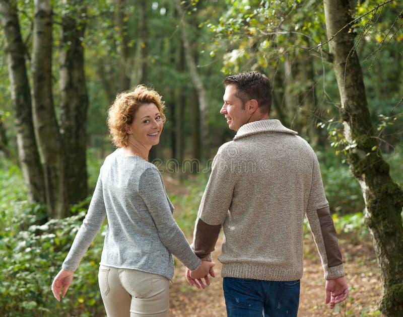 Счастливые пары держа руки и идя в лес стоковые фото