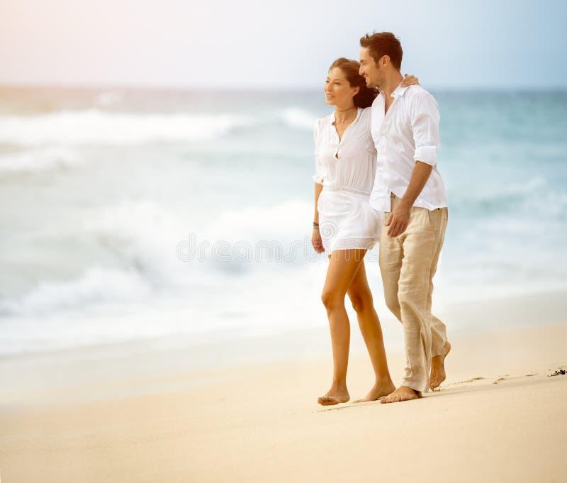 Счастливые пары держа руки идя на пляж стоковые изображения