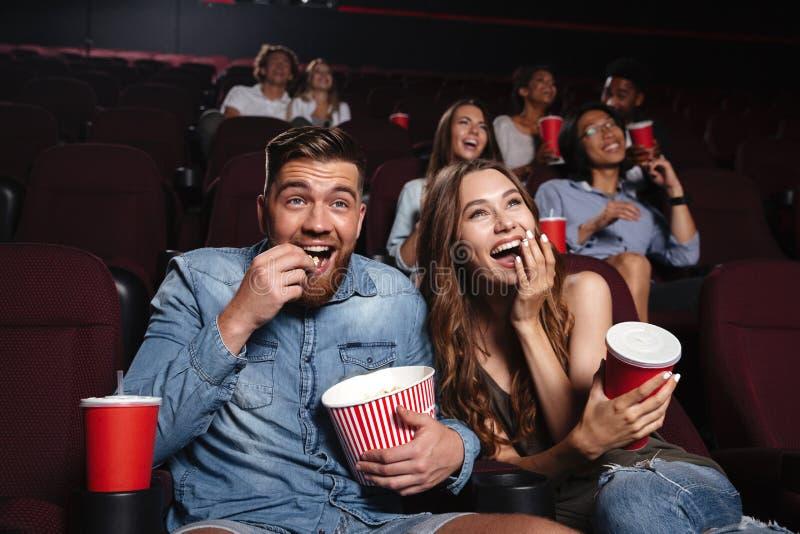 Счастливые пары есть попкорн и смеяться над стоковая фотография