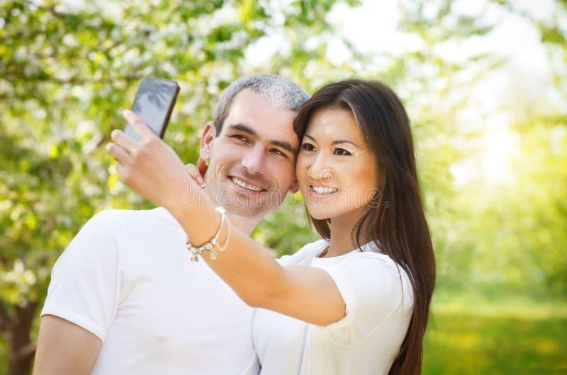 Счастливые пары делая фото selfie на smartphone outdoors стоковая фотография rf