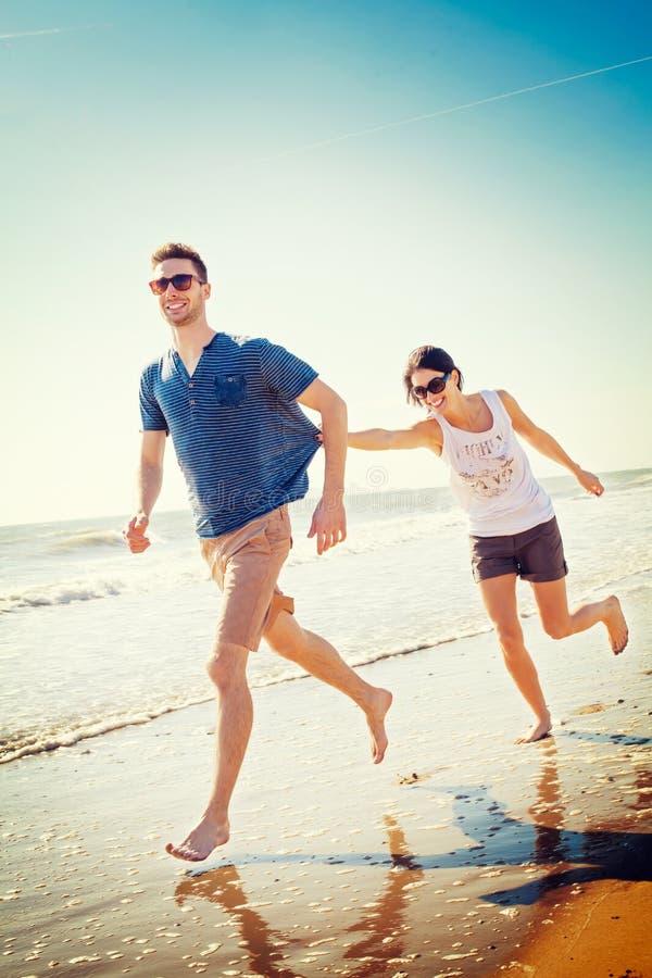 Счастливые пары играя на seashore стоковое фото rf