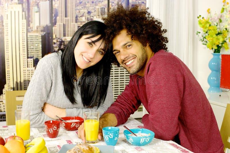 Счастливые пары имея завтрак перед небоскребами в городе смотря съемку средства камеры стоковое изображение