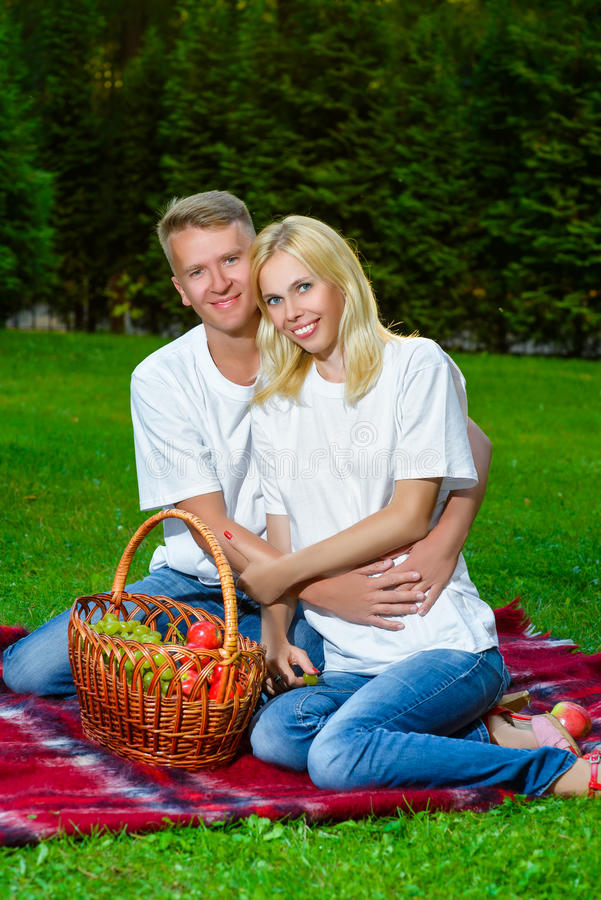 Счастливые пары имея пикник внешний на летний день стоковое изображение rf