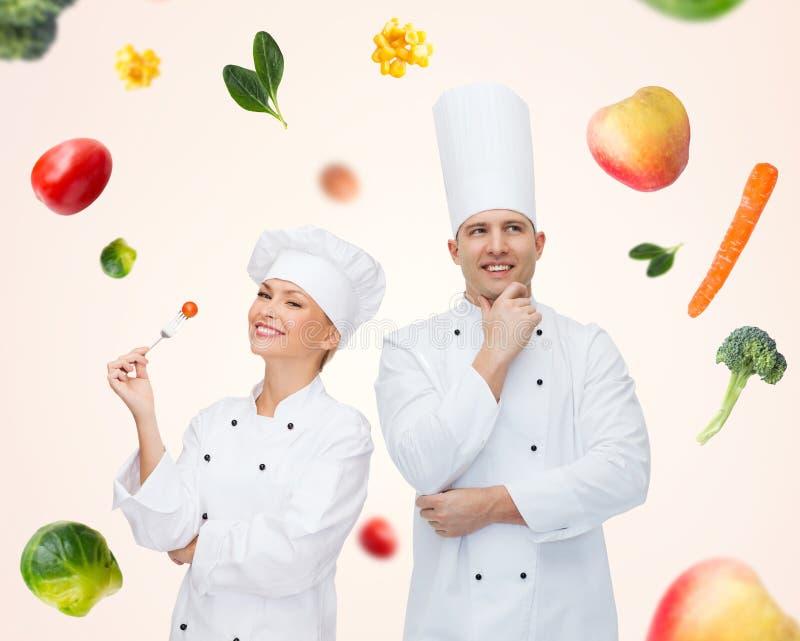 Счастливые пары или кашевары шеф-повара над предпосылкой еды стоковое фото