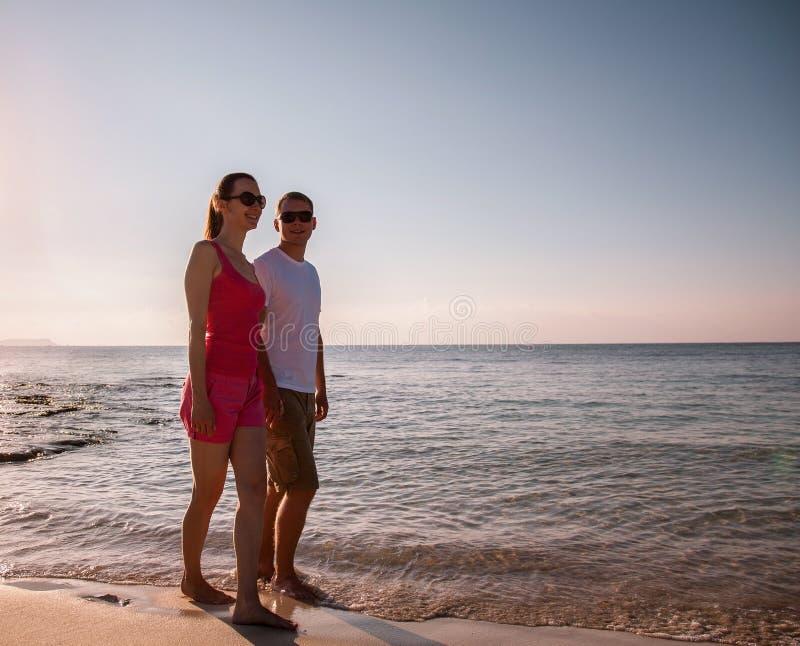 Счастливые пары идя вдоль seashore стоковое изображение