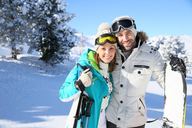 Счастливые пары на праздниках катания на лыжах стоковые фото