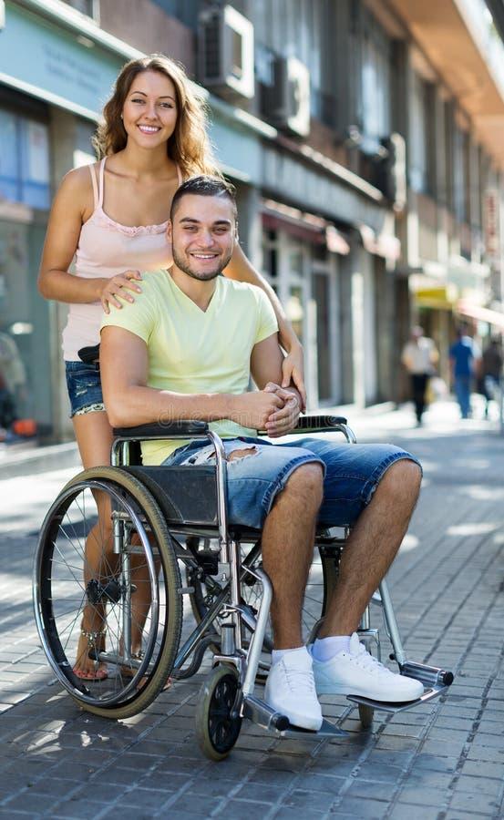 Счастливые пары на прогулке кресло-коляскы через город стоковое изображение