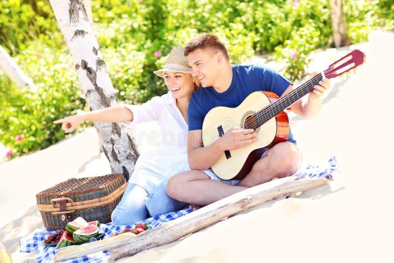 Счастливые пары на пляже с гитарой стоковые фотографии rf
