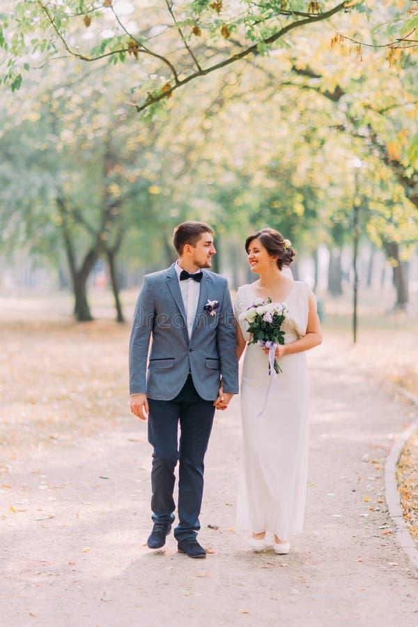 Счастливые пары новобрачных представляя outdoors идя на майну парка держа руки совместно и смеяться над стоковое изображение