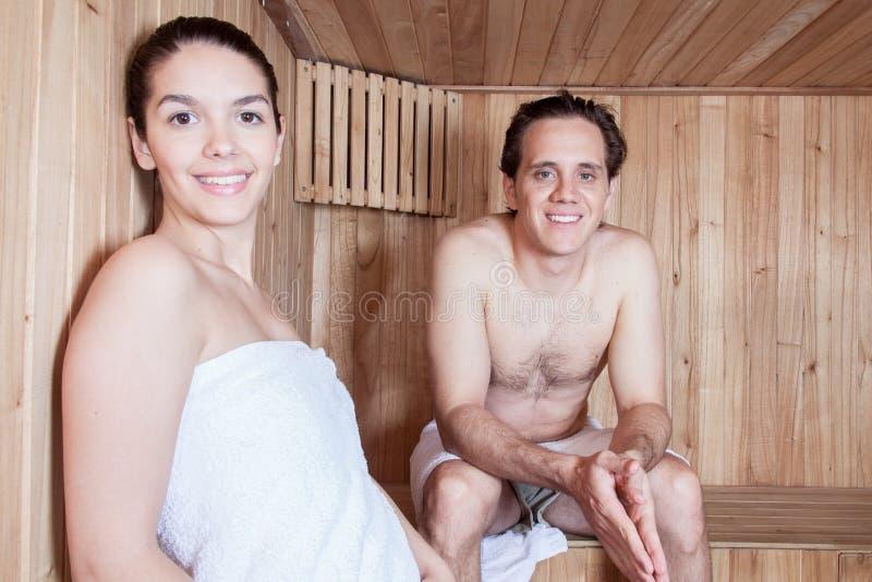 Счастливые пары ослабленные внутри сауны стоковая фотография