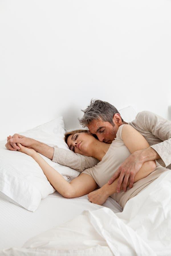 Счастливые пары отдыхая в кровати стоковое изображение