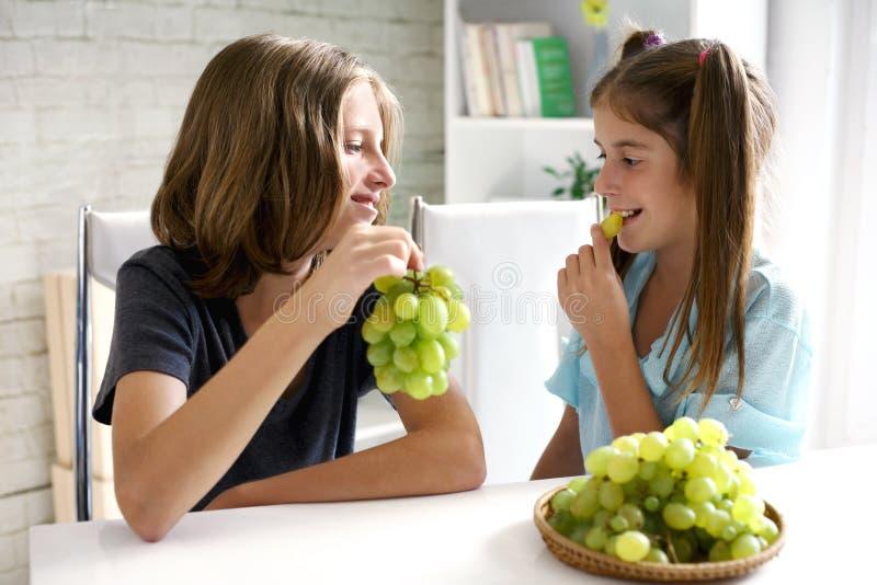Счастливые пары подростков есть виноградины стоковая фотография