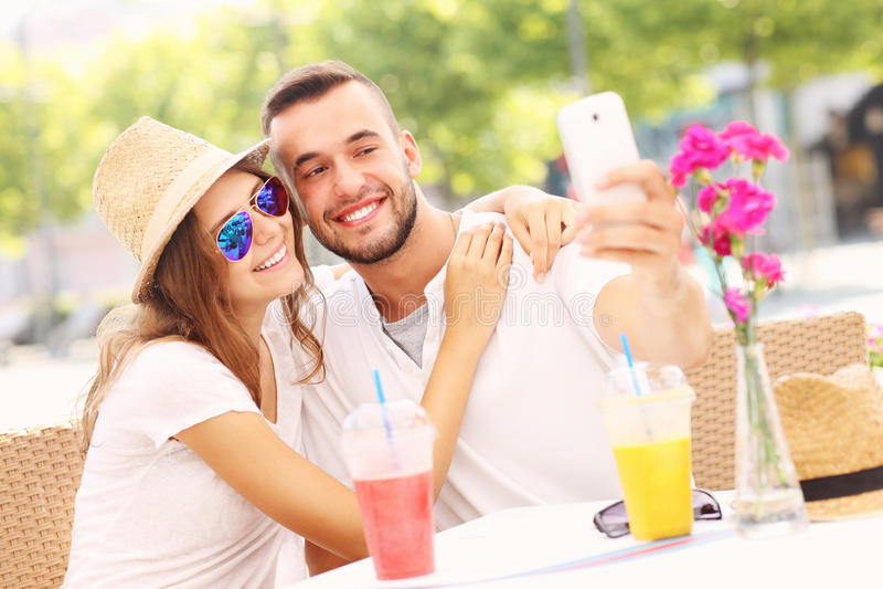 Счастливые пары принимая selfie в кафе стоковое фото rf
