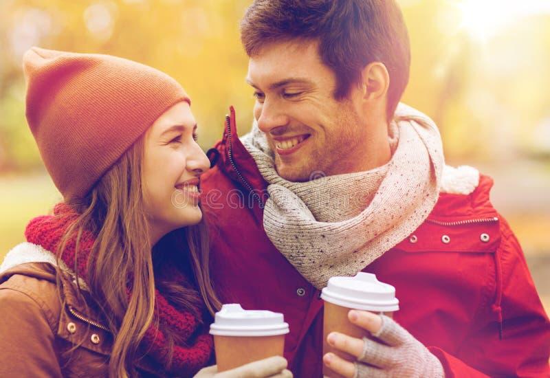Счастливые пары при кофе идя в осень паркуют стоковые изображения