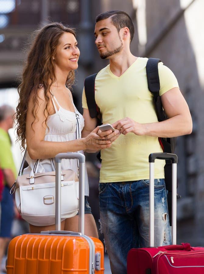 Счастливые пары путешественников находя путь с телефоном стоковое изображение