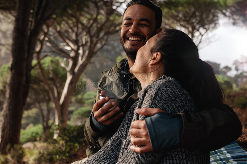 Счастливые пары располагаясь лагерем в лесе и имея кофе стоковое фото rf