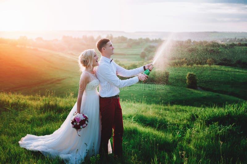 Счастливые пары свадьбы с buttle champaine стоковые фото