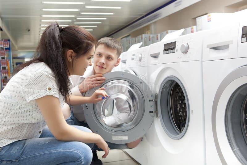 Счастливые пары семьи покупая новую стиральную машину стоковая фотография