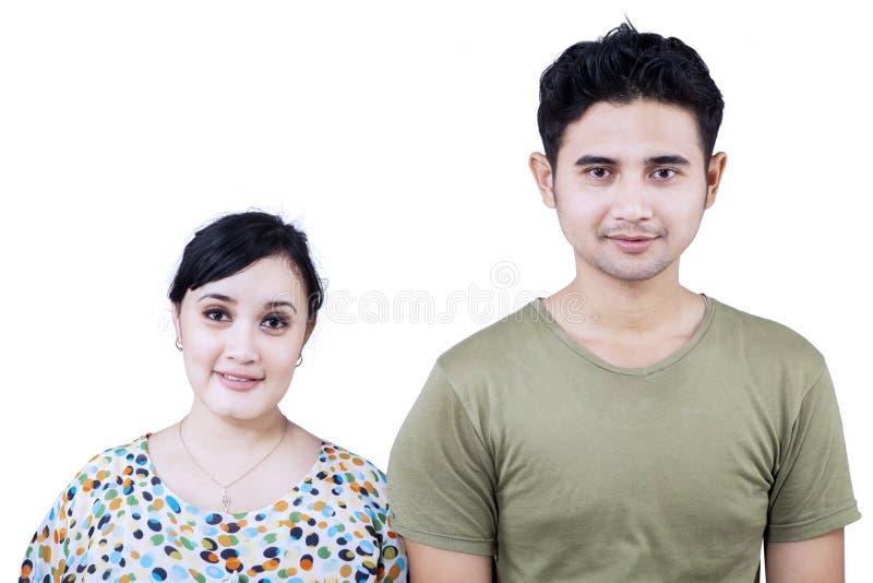 Счастливые пары смотря изолированную камеру - стоковое изображение rf