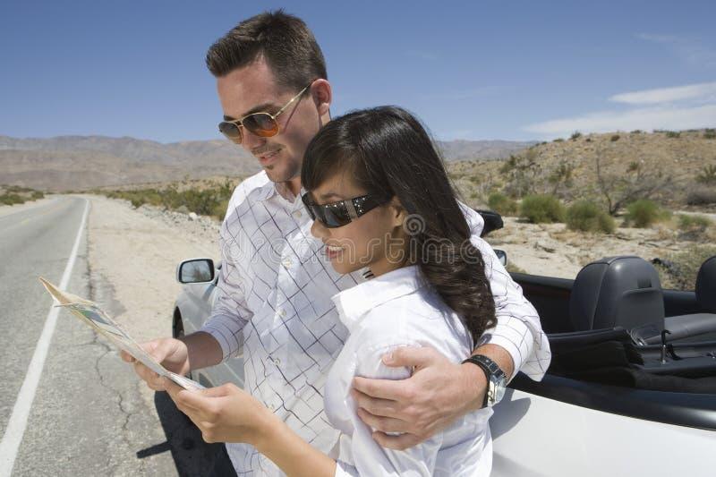 Счастливые пары смотря карту стоковое фото rf