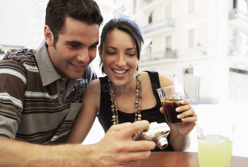 Счастливые пары смотря фотоснимки на цифровой фотокамера на тротуаре c стоковое фото rf