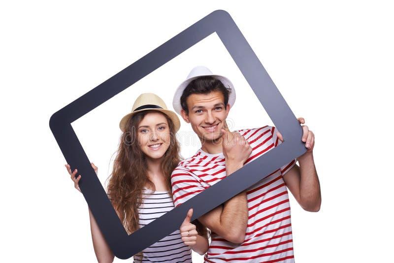 Счастливые пары смотря через рамку таблетки стоковое изображение rf