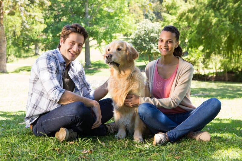 Счастливые пары с их собакой в парке стоковые изображения