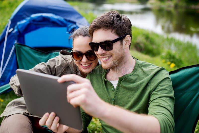 Счастливые пары с ПК таблетки на располагаясь лагерем шатре стоковые фотографии rf