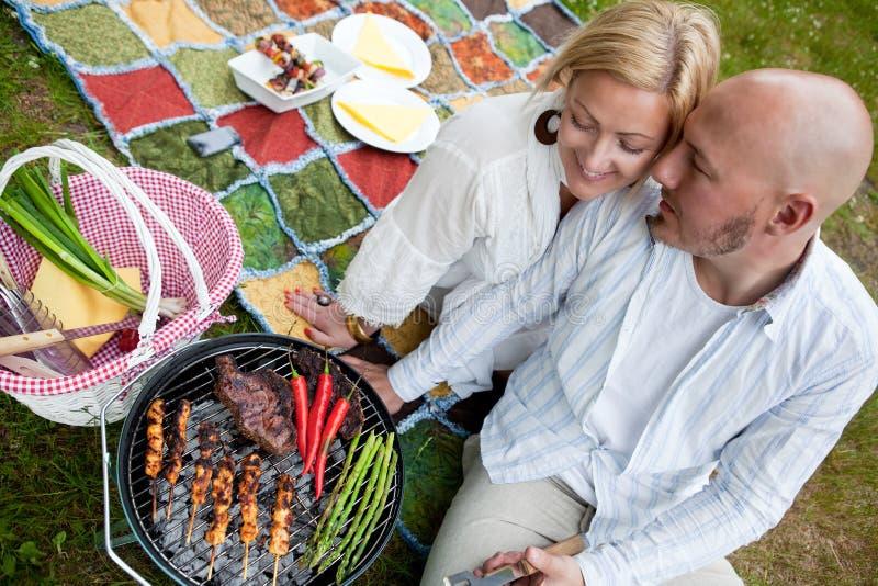 Счастливые пары с BBQ в парке стоковая фотография rf