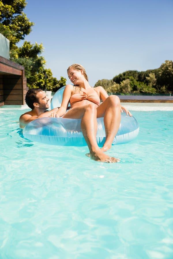 Счастливые пары с lilo в бассейне стоковое фото rf