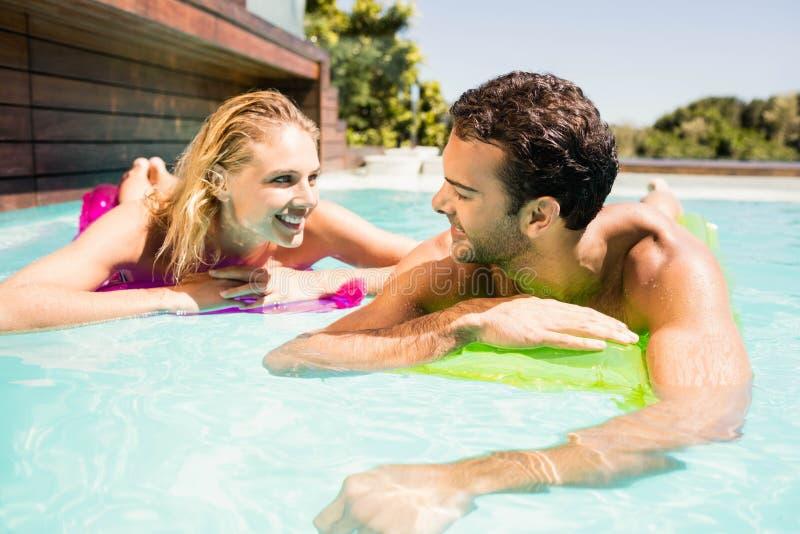 Счастливые пары с lilos в бассейне стоковые изображения