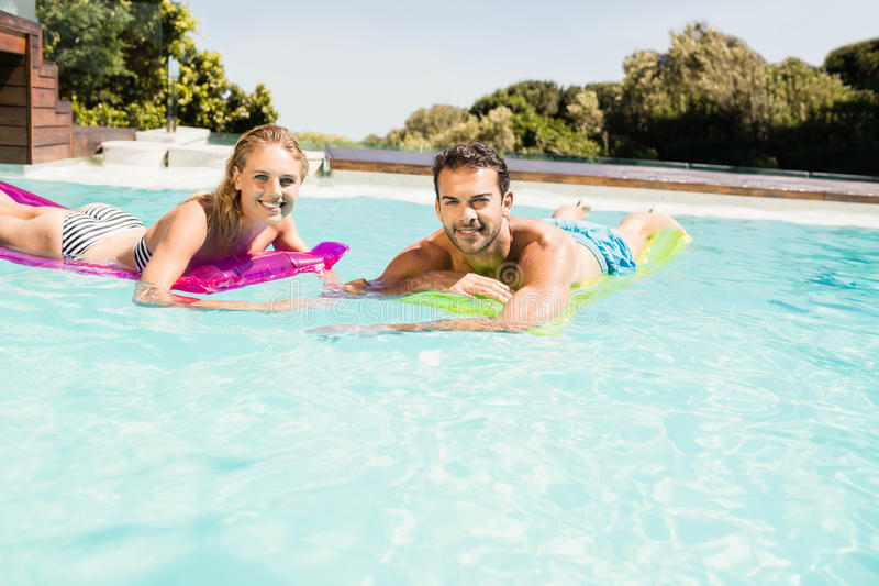 Счастливые пары с lilos в бассейне стоковое фото
