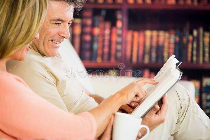 Счастливые пары читая книгу в читальном зале и выпивая coffe стоковые изображения rf
