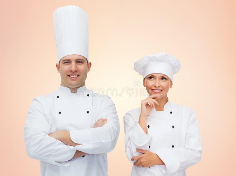 Счастливые пары шеф-поваров или кашеваров над бежевой предпосылкой стоковые изображения rf