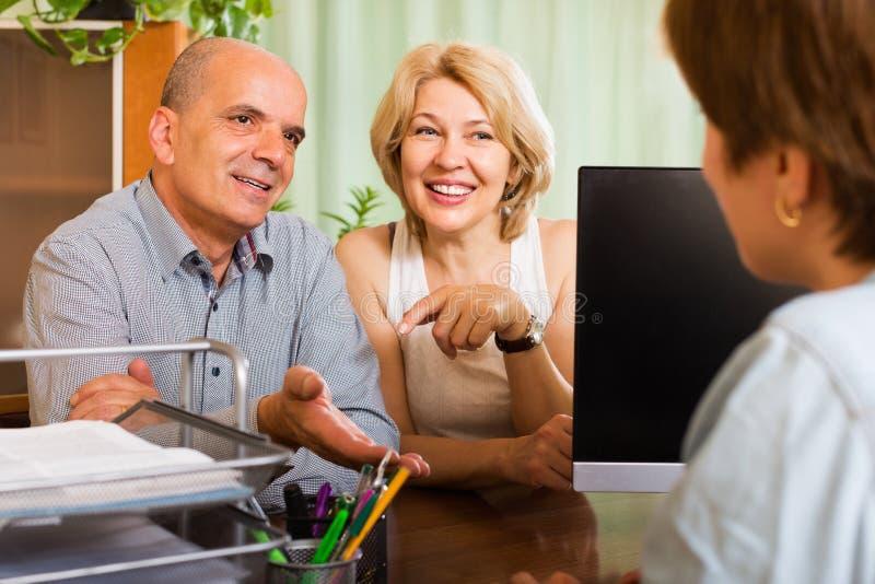 Счастливые пенсионеры разговаривая с менеджером стоковое изображение rf